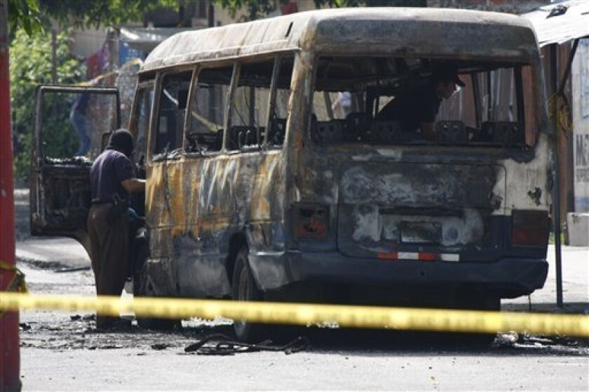A police officer inspects a burnt bus in San Salvador, Monday, June 21, 2010. The bus was attacked Sunday night while driving along its regular route in the northern area of San Salvador, killing at least 10 people who were aboard and leaving several others badly hurt. (AP Photo/Luis Romero)