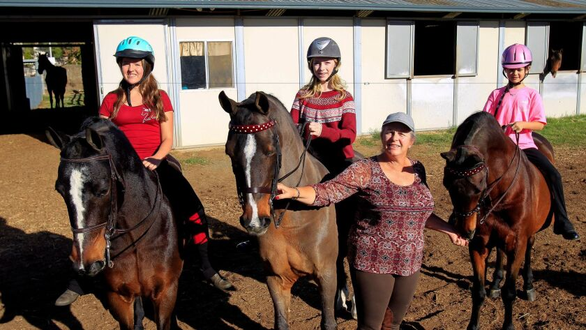 Trainer Ann Woulfe Miller with three of her World Champion Morgan equestrians Amanda White, 14, left, Katie Myron, 14, center, and Nini Hodge, 10, at Vista Valle Farms in Escondido.