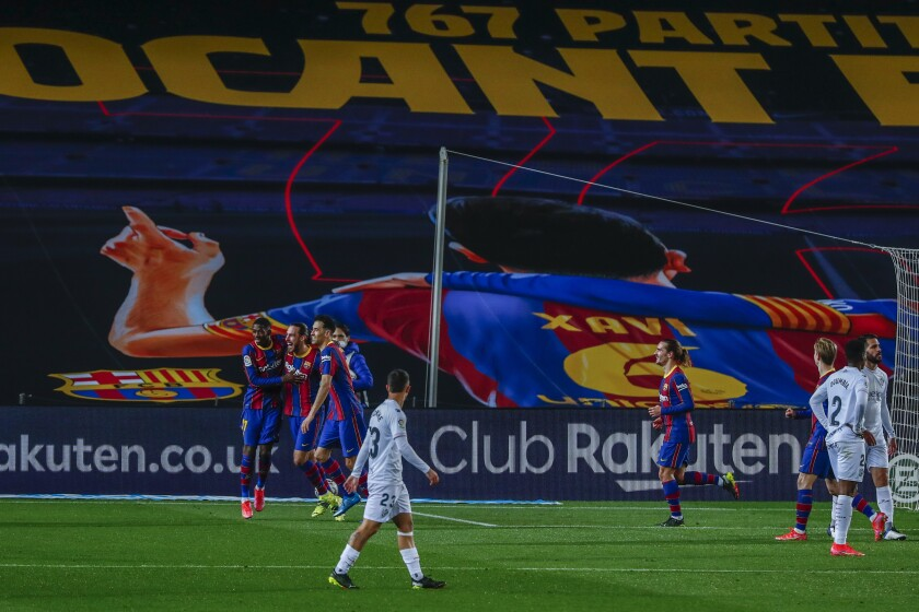 Barcelona's Oscar Mingueza, center left, celebrates after scoring his side's third goal during the Spanish La Liga soccer match between FC Barcelona and Huesca at the Camp Nou stadium in Barcelona, Spain, Monday, March 15, 2021. (AP Photo/Joan Monfort)