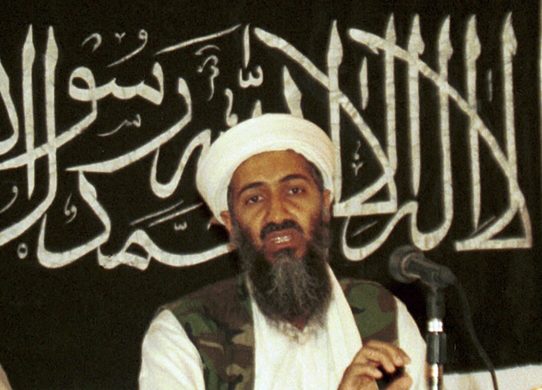 A bearded man in white turban and camouflage vest speaks before a microphone. Behind him is Arabic script on a dark backdrop.