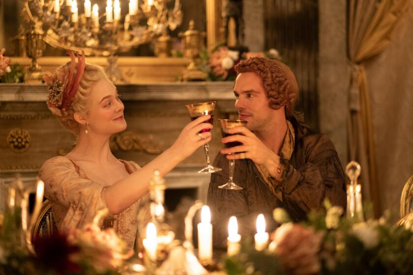 """Catherine (Elle Fanning) shares a toast with husband Peter III (Nicholas Hoult) in """"The Great."""""""