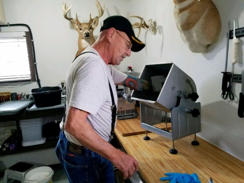 Myron Schlafman demonstrates how his arm got caught in the meat mixer.