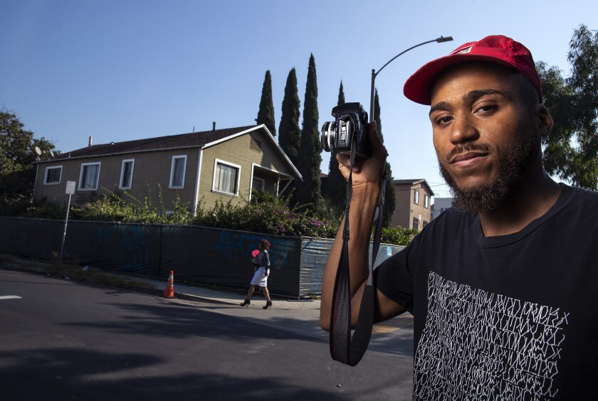 Photojournalist Lexis-Olivier Ray on Nov. 6 with an L.A. Craftsman-style building slated for demolition.