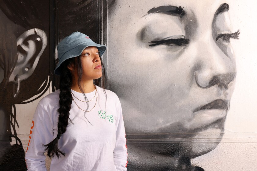 Alepsis Hernandez in front of her first paid commission, a mural showing a woman's face.