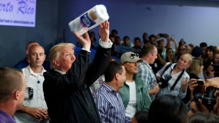 President Donald Trump tosses paper towels into a crowd like a basketball player taking a shot, at Calvary Chapel in Guaynabo, Puerto Rico on Oct. 3.