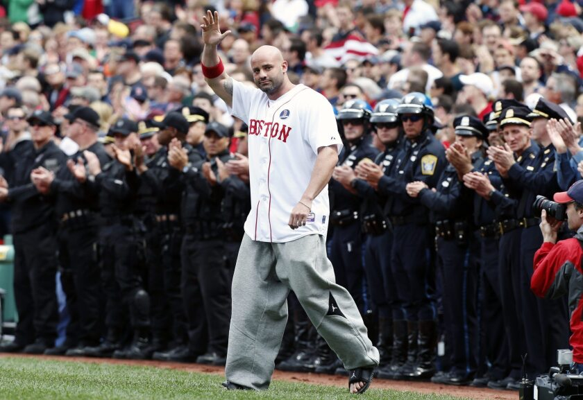Boston Marathon bombing victim Steven Byrne waves as he comes onto the field at fenway for a ceremonial first pitch before Saturday's game between the Boston Red Sox and the Kansas City Royals in Boston.