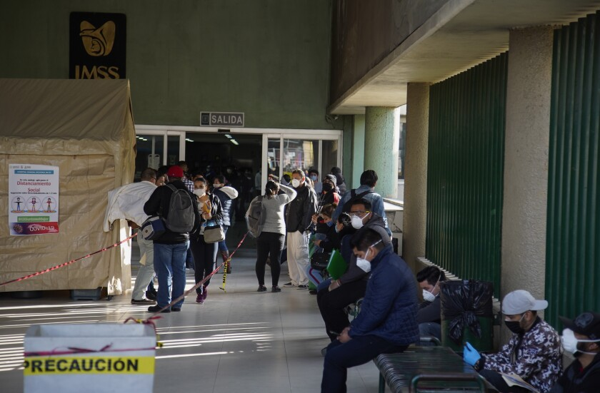 People wait outside a hospital in Tijuana a couple weeks ago for updates from staff. Tijuana hospitals are becoming overwhelmed by coronavirus patients.