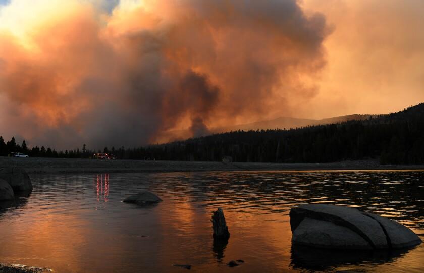 Thick smoke rises behind a lake.