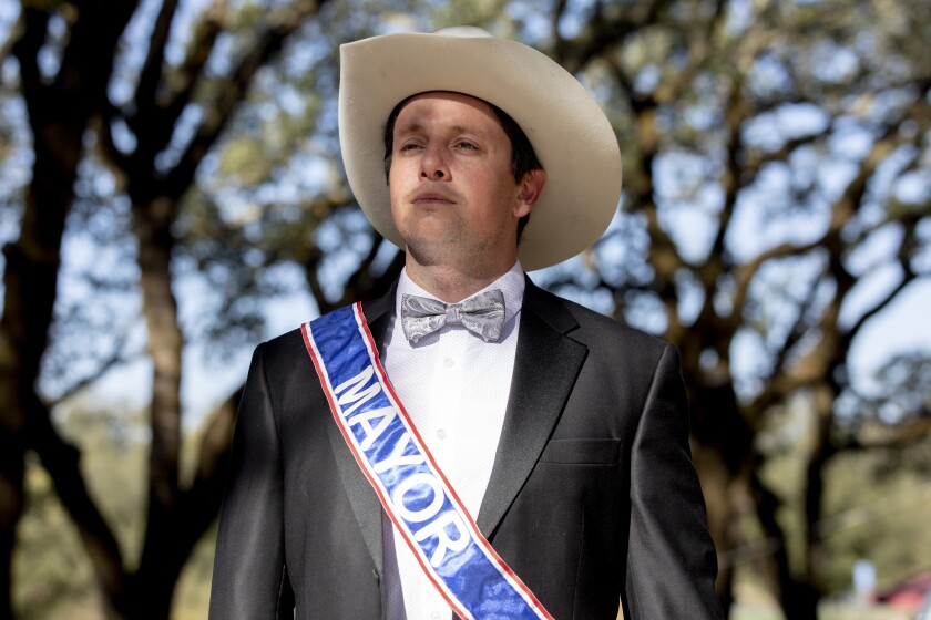 """Dominic Foppoli wears a suit with bow tie and a sash reading """"Mayor."""""""
