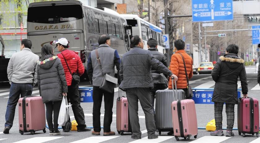 Chinese tourists wait for a bus in Tokyo's Ginza neighborhood.