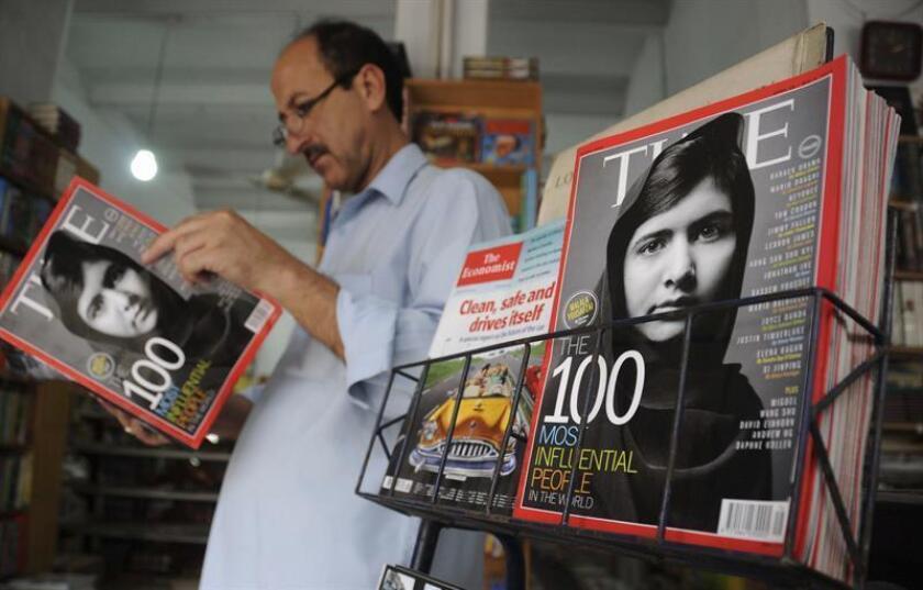Un hombre lee una copia de la revista TIME en una tienda en cuya portada aparece una fotografía de Malala Yousafzai. EFE/Archivo