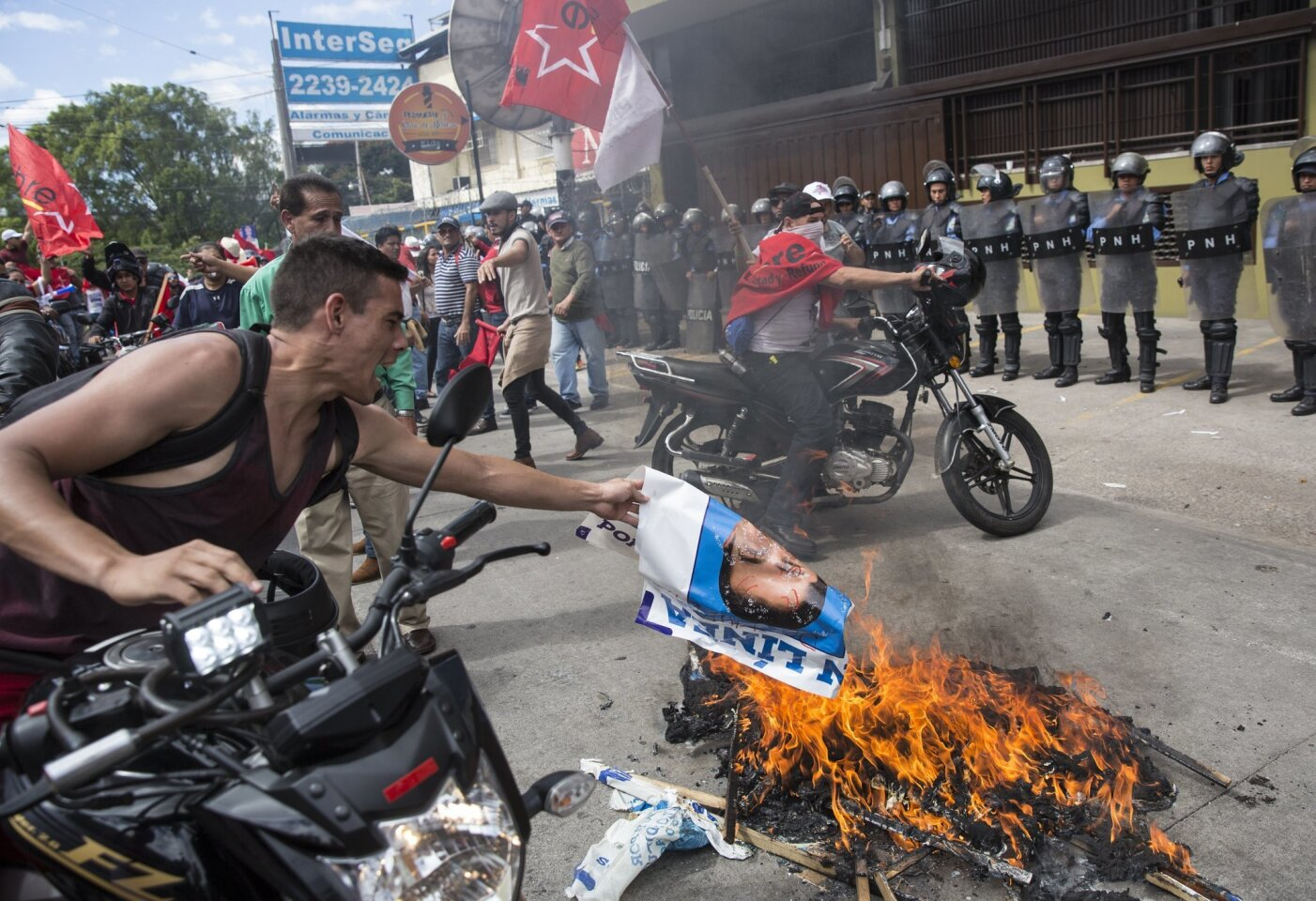 A supporter of Libre Alliance presidential candidate Salvador Nasralla adds to a bonfire of burning banners promoting Honduran President Juan Orlando Hernandez during a protest claiming electoral fraud outside the Supreme Electoral Tribunal in Tegucigalpa, Honduras.