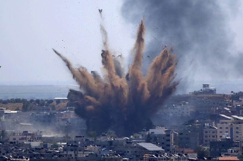 Humo y restos salen despedidos tras ataques aéreos israelíes contra un edificio en Gaza