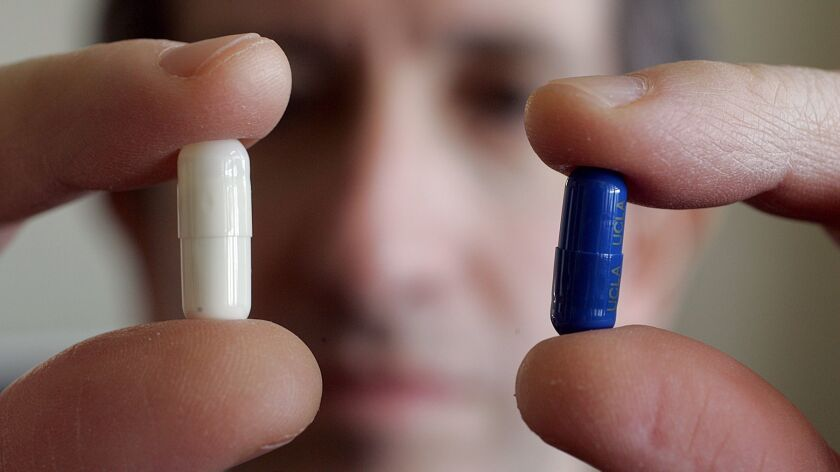 A UCLA professor studying the placebo effect holds up a placebo pill and some actual medication in this 2005 photo.