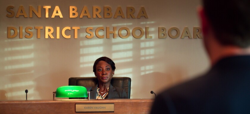 A woman sits in a chair under a sign that says Santa Barbara District School Board.