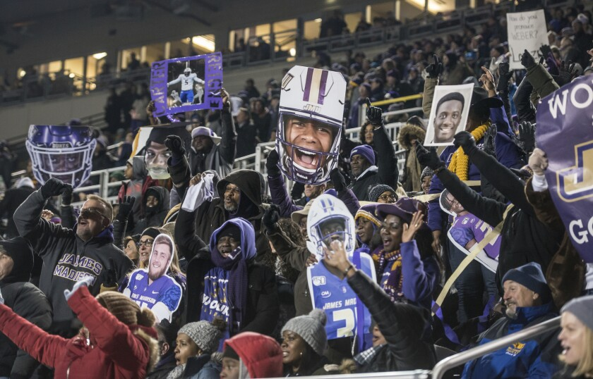 FILE - In this Dec. 21, 2019, file photo, James Madison fans cheer on their team during the second half of a semifinal against Weber State in the NCAA Football Championship Subdivision college playoffs in Harrisonburg, Va. As the college football season ramps up in three major conferences and among other programs scattered across the country, there will be a void at the Football Championship Subdivision level -- very few games and no scheduled playoffs. (Daniel Lin/Daily News-Record via AP, File)