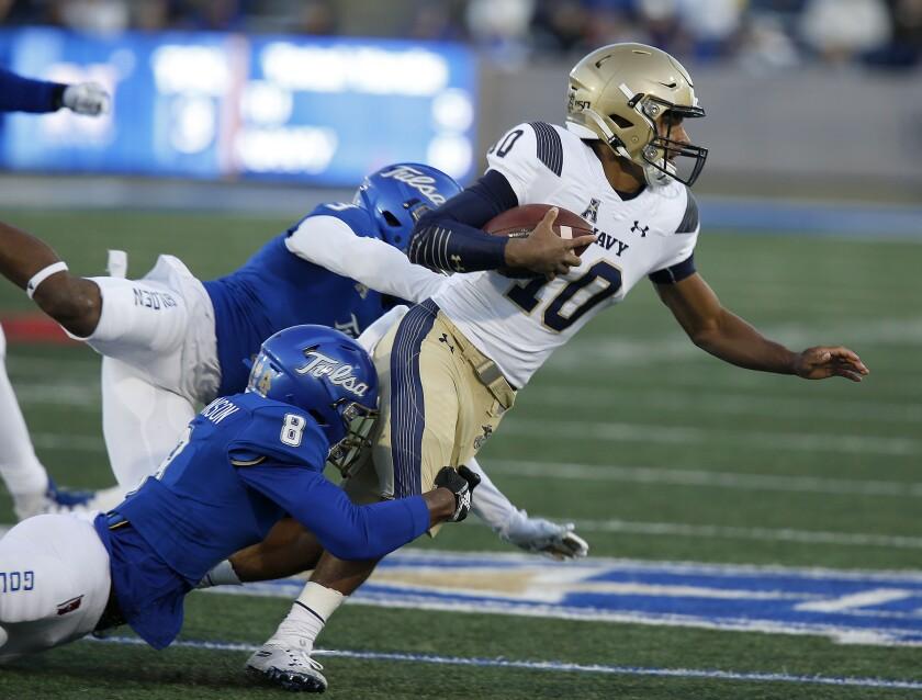 Tulsa's Cristian Williams and Brandon Johnson (8) bring down Navy quarterback Malcolm Perry (10) during an NCAA college football game, Saturday, Oct. 12, 2019, in Tulsa, Okla. (Stephen Pingry/Tulsa World via AP)