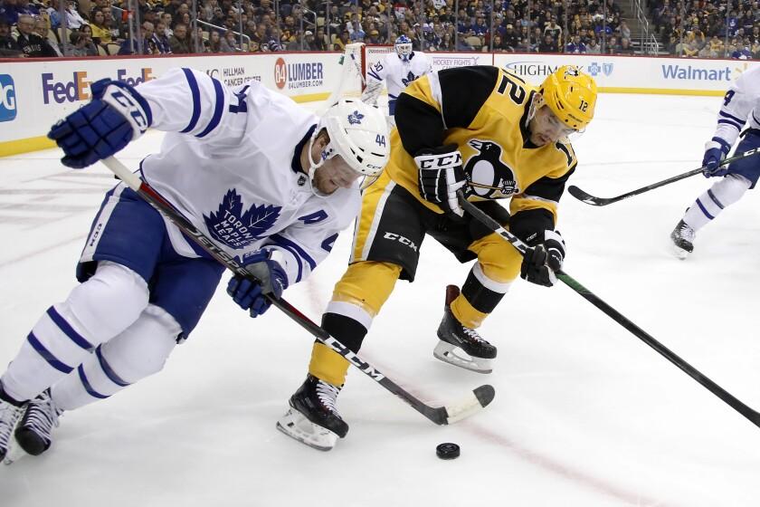 Toronto Maple Leafs' Morgan Rielly (44) battles Dominik Simon (12) for the puck during the second period of an NHL hockey game in Pittsburgh, Saturday, Nov. 16, 2019. (AP Photo/Gene J. Puskar)