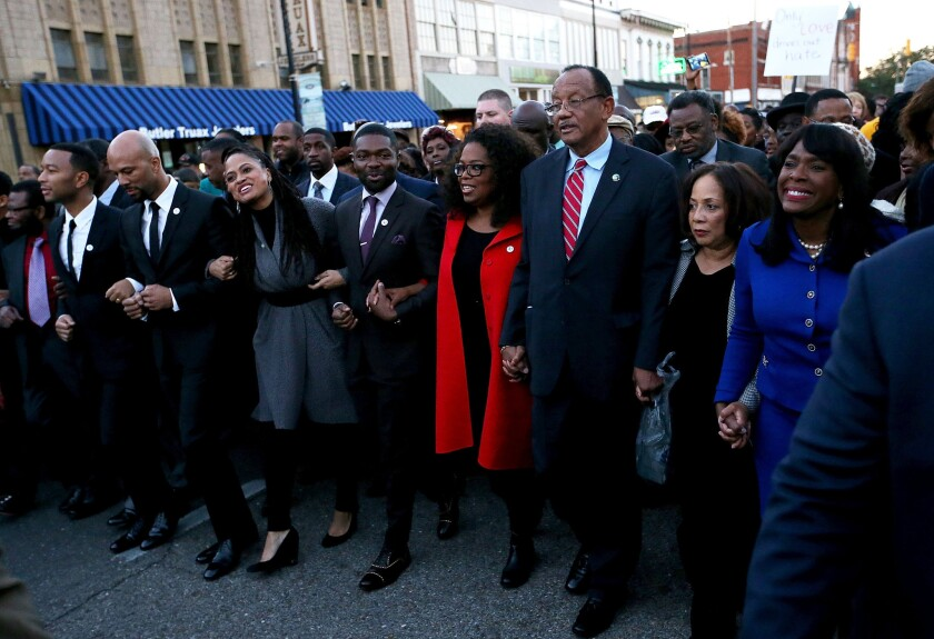 """Oprah Winfrey, in red, leads a Martin Luther King Jr. Day march in Selma, Ala., with cast and crew of the film """"Selma."""" They include, to the left of Winfrey, actor David Oyelowo, director Ava DuVernay, actor and songwriter Common and singer and songwriter John Legend."""