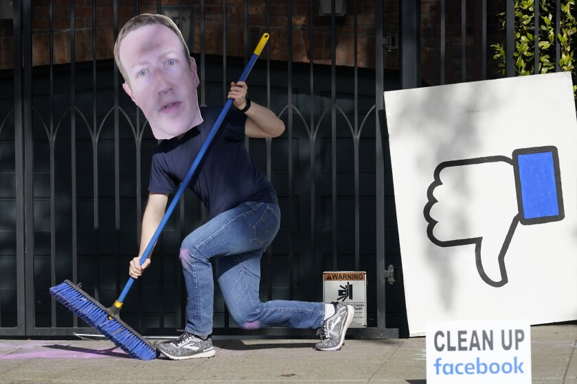 A man wearing a Mark Zuckerberg mask protests outside the Facebook chief executive's home in San Francisco.