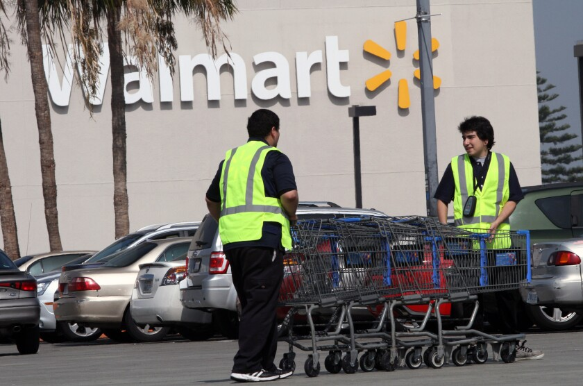 Workers retrieve shopping carts at the Crenshaw Plaza Wal-Mart in Los Angeles.