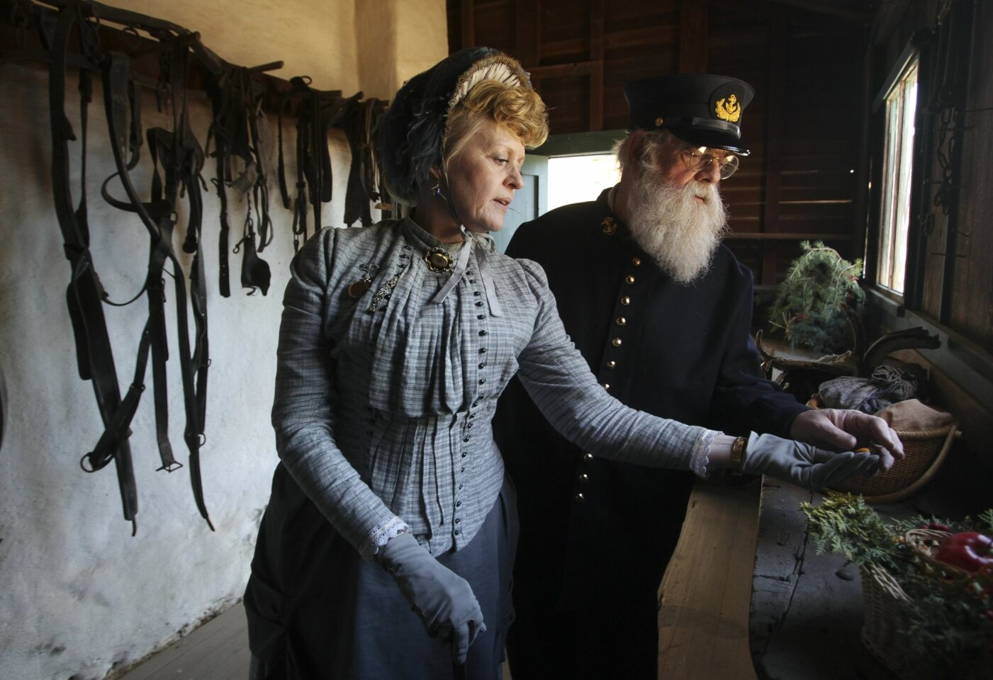 Bob Munson wears the uniform of a steam ship captain while his wife Nancy Munson wears clothing from 1887 as they look at items in the tack room during Rancho Christmas 2013 at the Rancho Guajome Adobe County Park in Vista on Sunday, December 1, 2013.