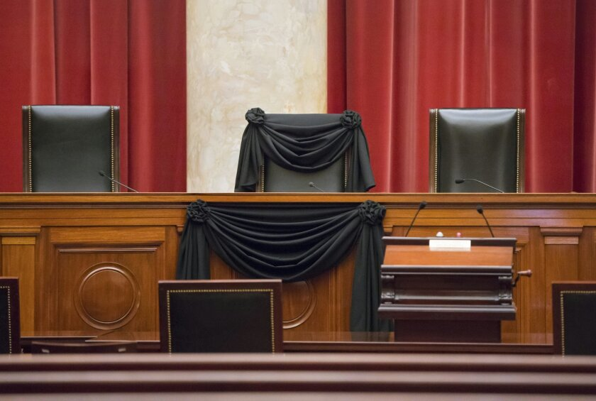 Supreme Court Justice Antonin Scalia's courtroom chair is draped in black to mark his death as part of a tradition that dates to the 19th century, Tuesday, Feb. 16, 2016, at the Supreme Court in Washington. Scalia died Saturday at age 79. He joined the court in 1986 and was its longest-serving just