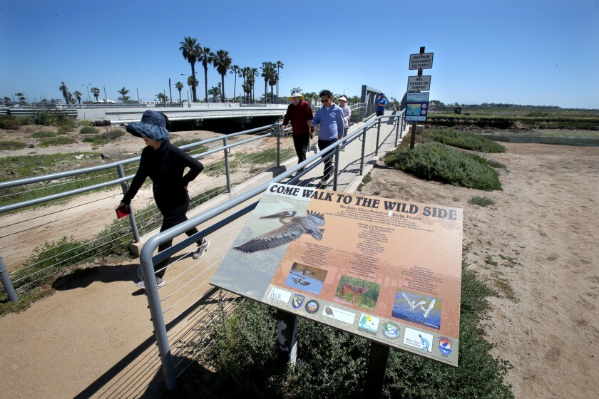 Visitors at the Bolsa Chica Conservancy Interpretive Center cross a pedestrian bridge during an Earth Day event this year.