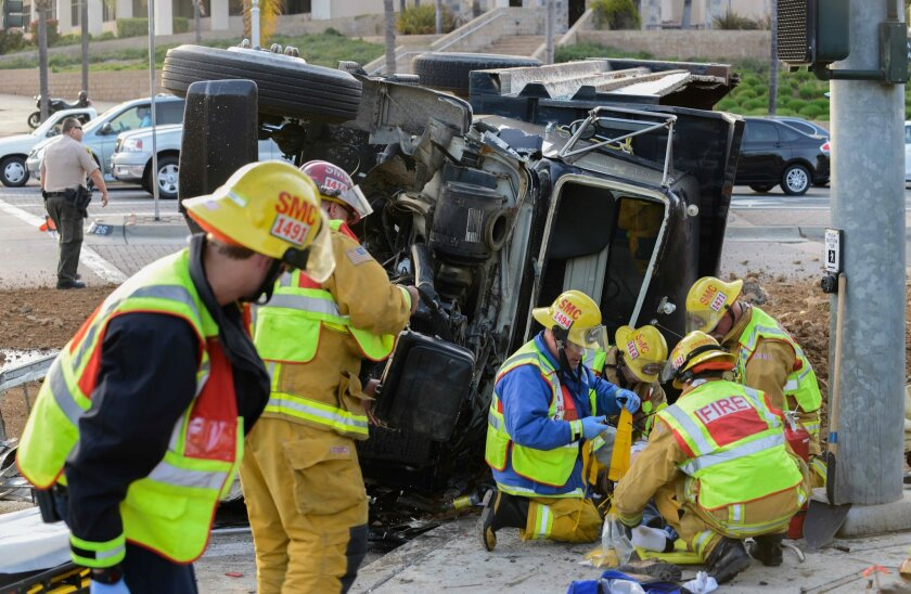 Firefighters prepare the driver of the dump truck to be loaded into a waiting ambulance in San Marcos|