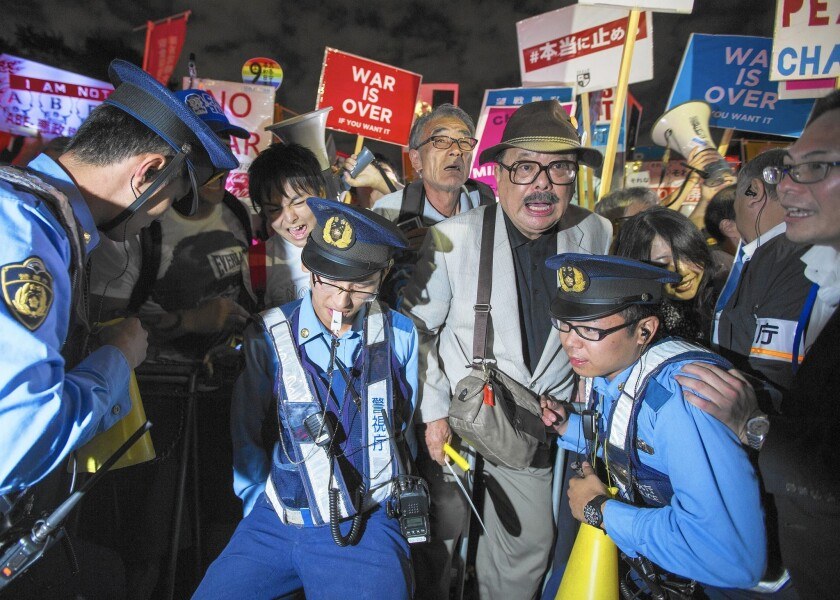 Japanese police hold back demonstrators outside the parliament building in Tokyo protesting legislation that would expand the powers of the pacifist nation's military.