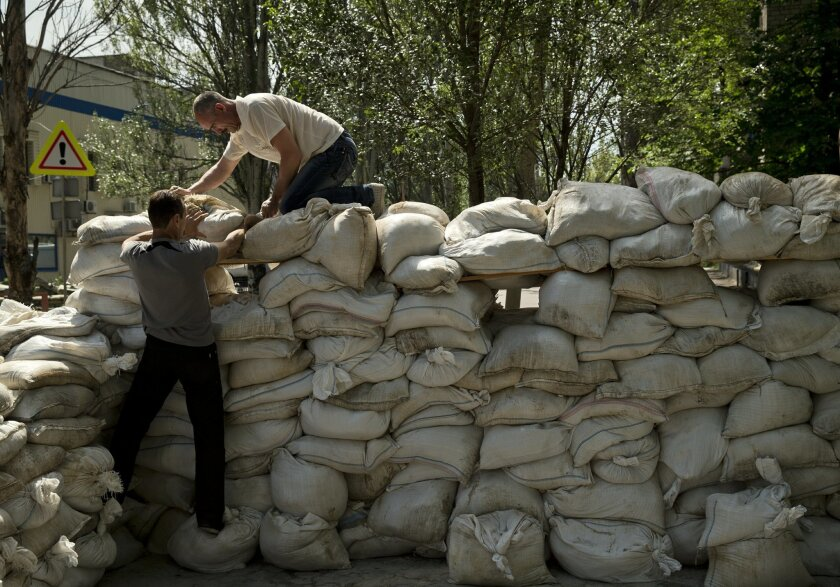 People pile up sand bags to set up a shooting position on the road leading from the airport to Donetsk, Ukraine, Tuesday, May 27, 2014. The eastern city of Donetsk was in turmoil Tuesday a day after government forces used fighter jets to stop pro-Russia separatists from taking over the airport. The