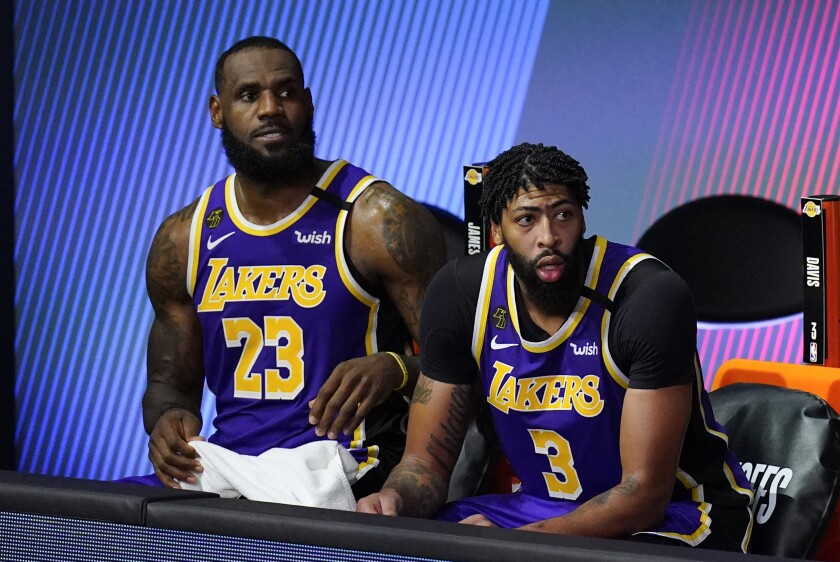 LeBron James and Anthony Davis watch from the bench in the second half of the Lakers' Game 1 loss to the Rockets on Friday.