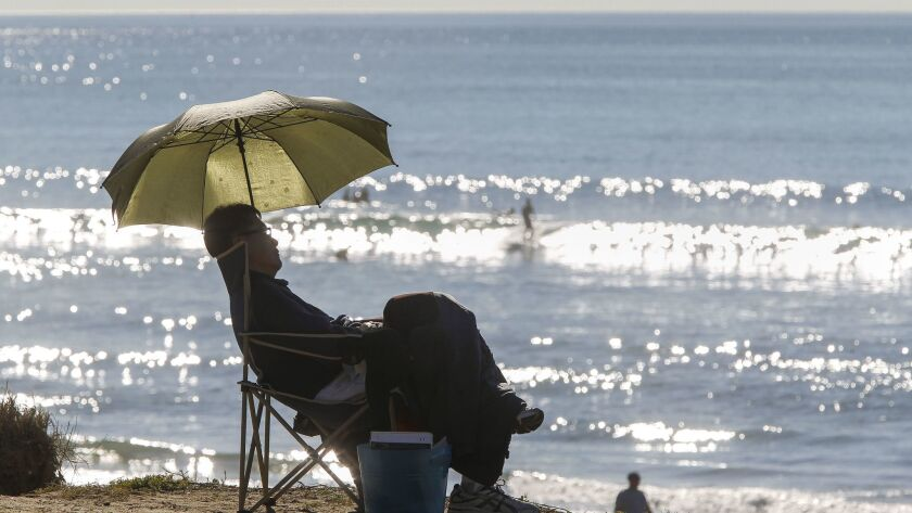 January 6, 2015, Del Mar, CA | Del Mar resident Oliver Chan relaxes in the shade of his umbrella whi
