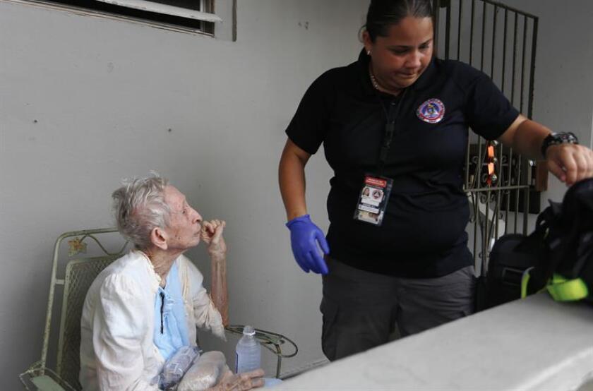 Una paramédico atiende a la anciana Marina Fernández (i) a dos días del paso del huracán María, en San Juan (Puerto Rico). EFE/Archivo