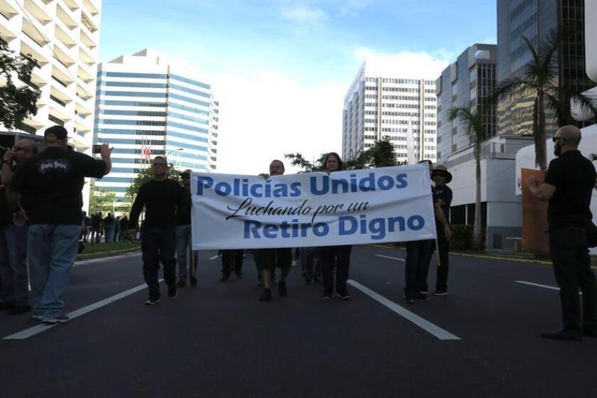 Policías de Puerto Rico se manifiestan hoy, lunes 22 de enero de 2018, frente a las oficinas de la Junta de Supervisión Fiscal (JSF) en San Juan (Puerto Rico) para reclamar una jubilación digna y el pago de horas extras. EFE