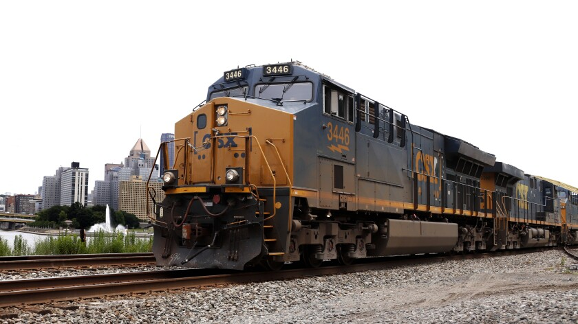 FILE - In this June 24, 2019, file photo, a CSX freight train rolls past downtown Pittsburgh. The biggest U.S. freight railroads appear ready to renew their push to reduce their crews to one-person from the current two-man operation used at major railroads now. Eight U.S. railroads have filed a federal lawsuit against the union that represents rail conductors to force the SMART union to negotiate about crew sizes during the next round of contract talks that starts in November. (AP Photo/Gene J. Puskar, File)