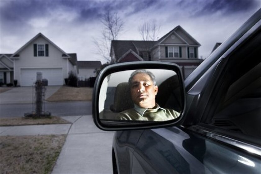 Venkat Thannir poses in his 2010 Toyota Camry at his home Tuesday, Feb. 9, 2010, in Lexington, S.C. In the Fall, Thannir's car accelerated on it's own as he was pulling out of a parking lot in a Burger King in North Carolina. He has not taken his car in for the recall. (AP Photo/Anne McQuary).