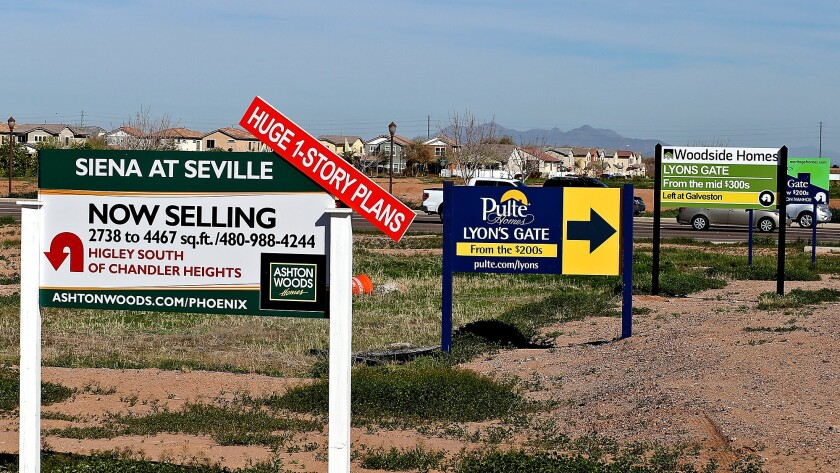 Signs advertising new housing developments are posted in Gilbert, Ariz. Residents of L.A. and Orange