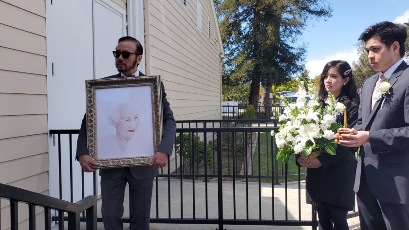 Viet Le holds a portrait of his beloved mother, Thai Thanh, following a private funeral procession for the singer in Westminster.