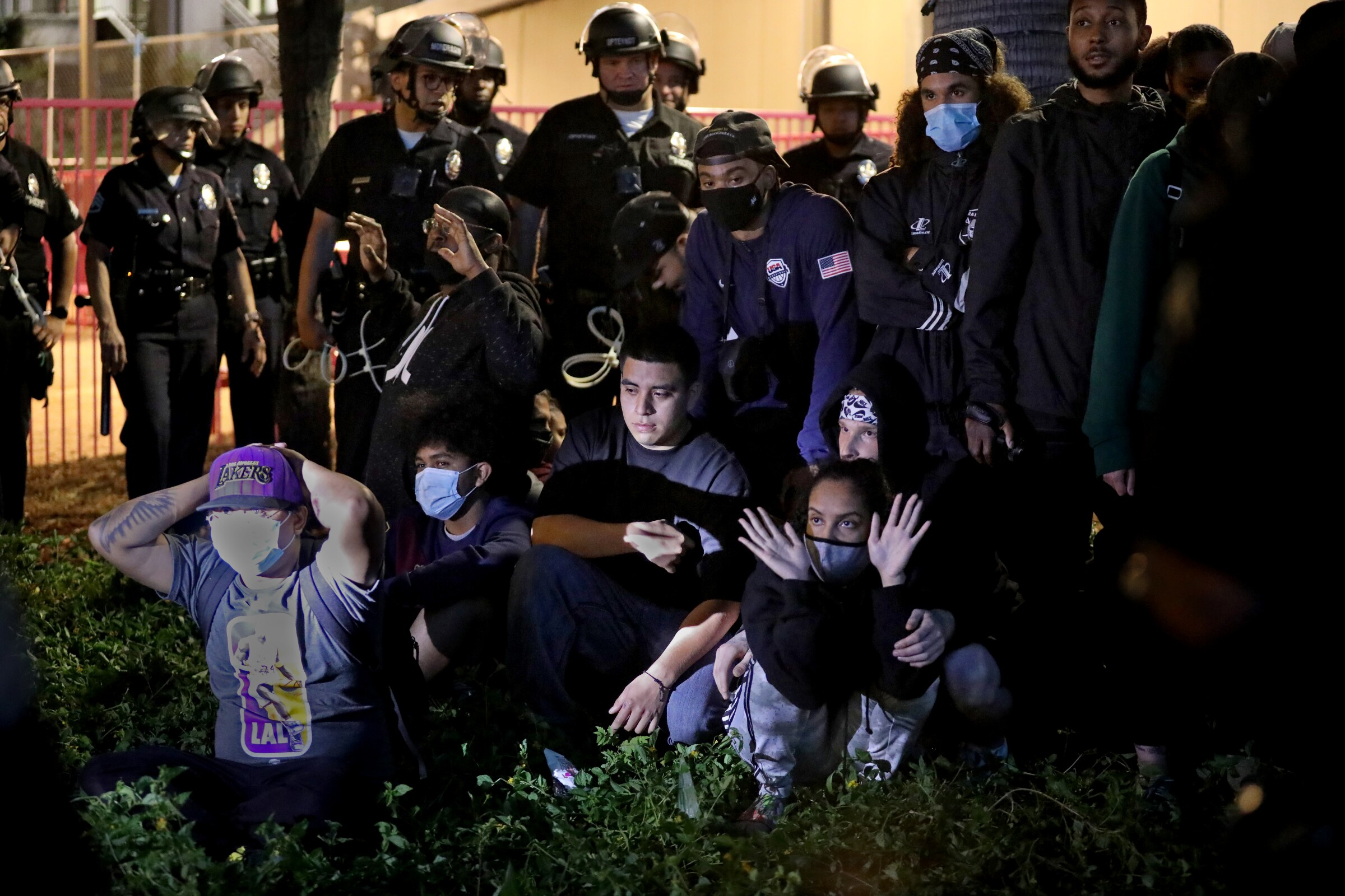 Police in helmets stand behind a group of arrestees who are seated on the ground