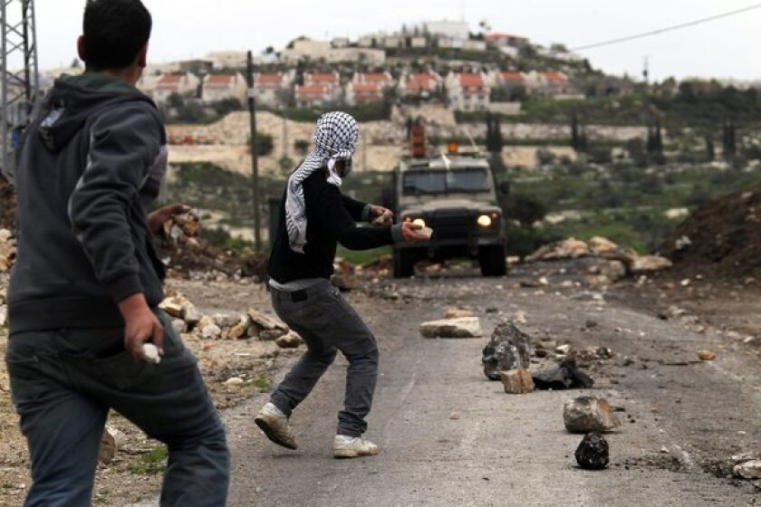 Palestinians hurl stones at Israeli soldiers during the weekly protest against the Jewish settlement of Qadomem, near Nablus, in the West Bank. Middle East analysts fear a third intifada, or uprising, is brewing in the occupied territories as Palestinians lose hope for any resumption of the peace process.