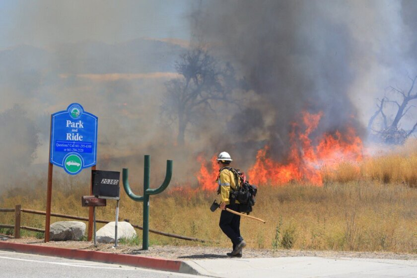 A fast-moving wildfire has triggered evacuations and shut down the 14 Freeway in the Santa Clarita Valley.