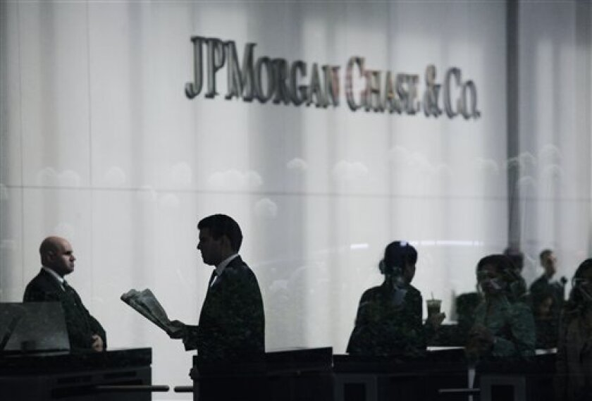 FILE - In this May 14, 2012, file photo, people arrive at JPMorgan Chase headquarters in New York. Legal troubles and regulatory scuffles keep piling up for the banking industry, a fact that's sure to drag down results when the banks start reporting fourth-quarter earnings beginning Friday, Jan. 11, 2013. (AP Photo/Mark Lennihan, File)