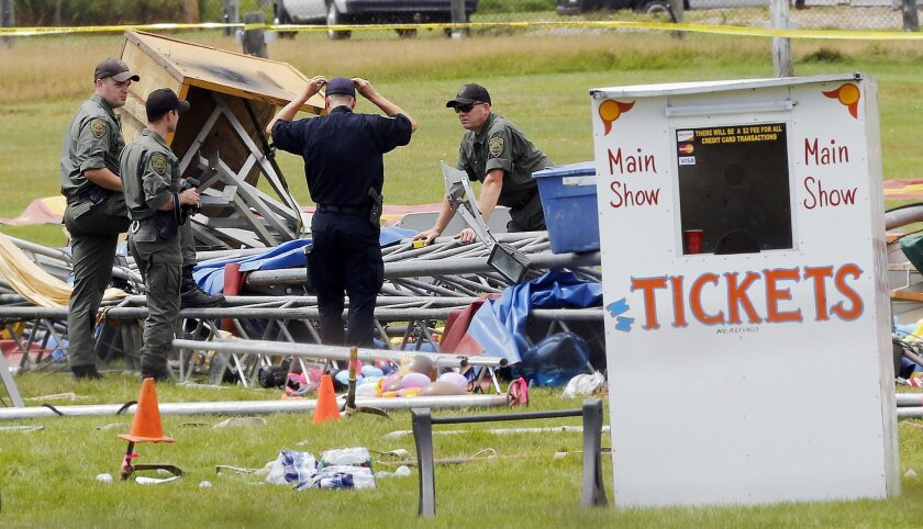 FILE - In a Aug. 4, 2015 file photo, investigators work at the scene of a circus tent that collapsed, killing a father and his 6-year-old daughter in Lancaster, N.H. Federal safety officials have proposed more than $33,000 in fines against a Florida-based circus operator for the tent collapse. The