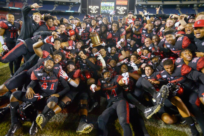 San Diego State safety Dwayne Johnson Jr. holds the Old Oil Can Trophy surrounded by teammates after after SDSU's victory Friday night over Fresno State at SDCCU Stadium. The winner retains the trophy until the next meeting between the teams.