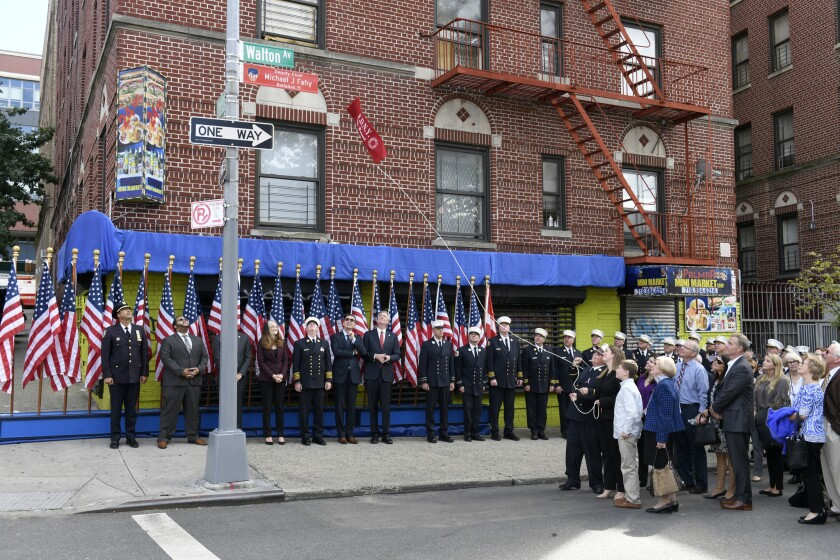 Family and dignitaries reveal a street sign during a plaque dedication and street sign unveiling ceremony in honor of FDNY Deputy Chief Michael Fahy. Thursday, in the Bronx, New York.
