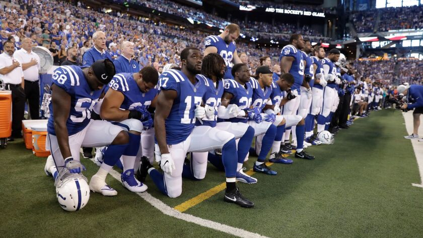 Members of the Indianapolis Colts take a knee during the Nation Anthem before an NFL football game a