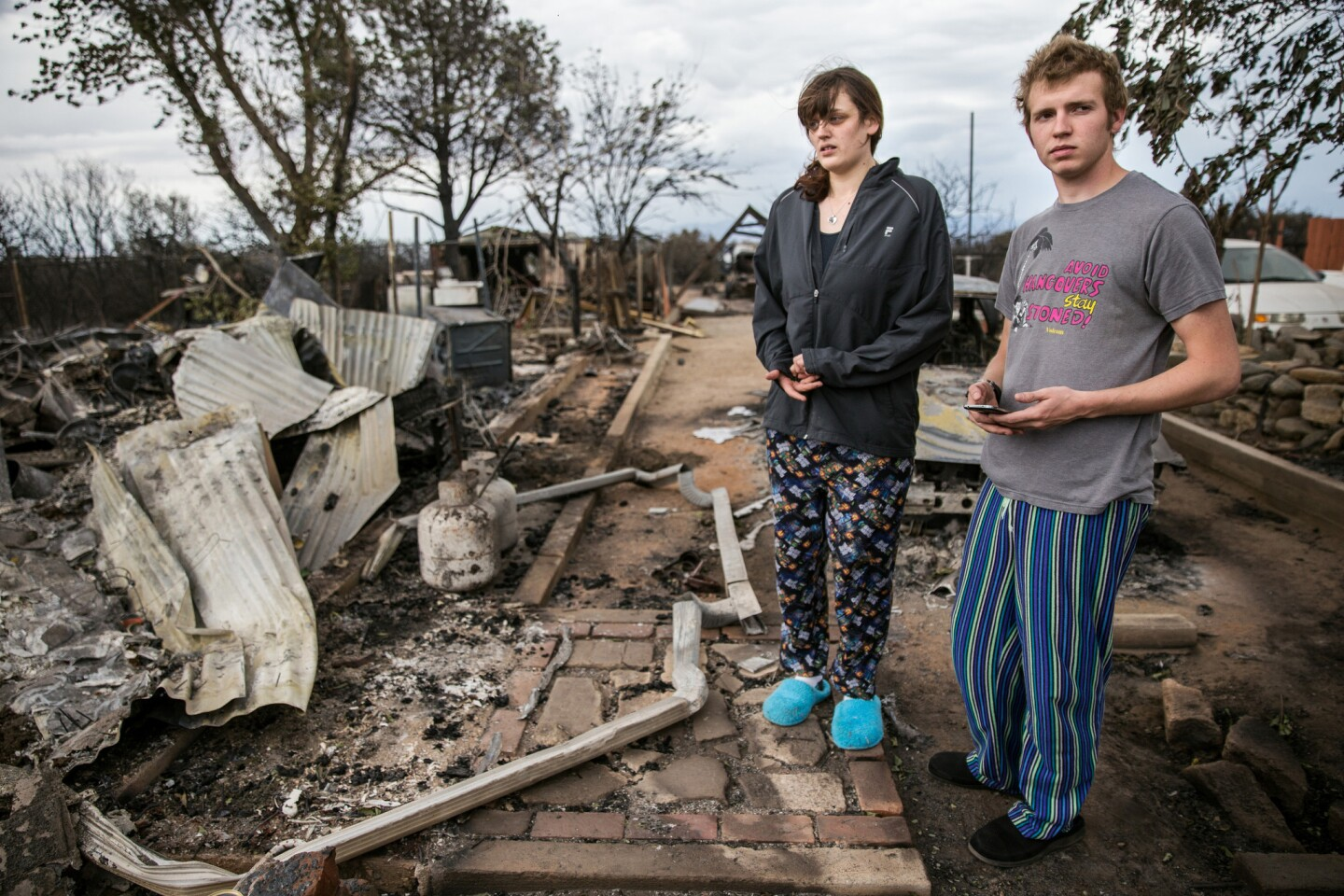 Andrew Eblen and his fiancee, Britany Carpenter, examine the ruins of their home, which was destroyed in the North fire. The couple recently renovated the home, Eblen's childhood residence, and was going to move in in a few months.