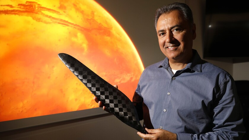 Wahid Nawabi, chief executive of AeroVironment Inc., holds a scale model of one of the composite blades that will be used to propel NASA's Jet Propulsion Laboratory Mars Helicopter through the thin Martian atmosphere.