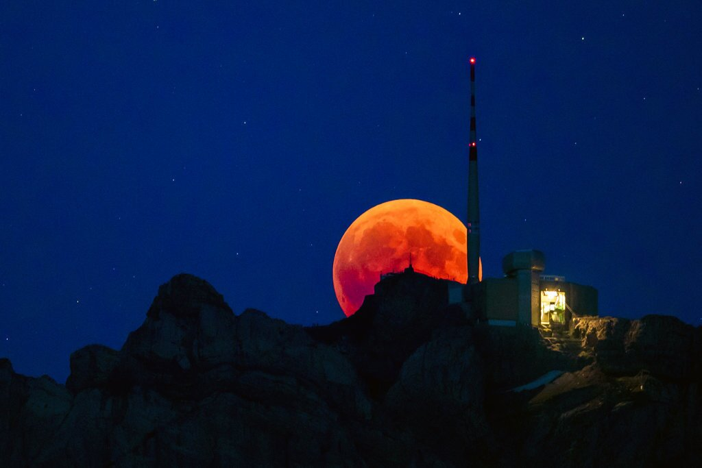 The moon turns red during a total lunar eclipse, behind the Saentis in Luzern, Switzerland, Friday, July 27, 2018. Skywatchers around much of the world are looking forward to a complete lunar eclipse that will be the longest this century.